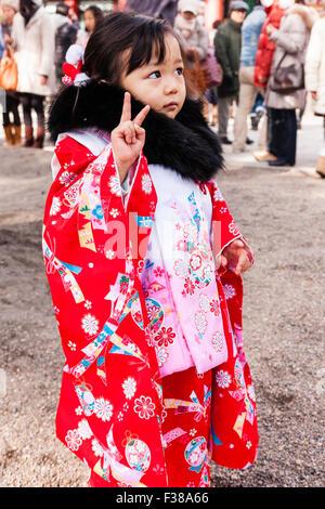 Face triste enfant japonais, fille, 4-5 ans. Porter du rouge et rose kimono avec col de fourrure noire à la nouvelle Banque D'Images