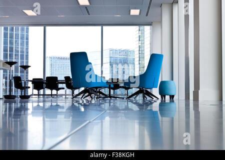 Tourbillonné bleu moderne chaises de bureau dans une grande pièce ouverte avec de grandes fenêtres et l'extérieur Banque D'Images
