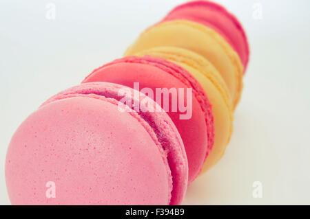 Libre de quelques macarons appétissants de couleurs pastel et de saveurs différentes sur un fond blanc Banque D'Images