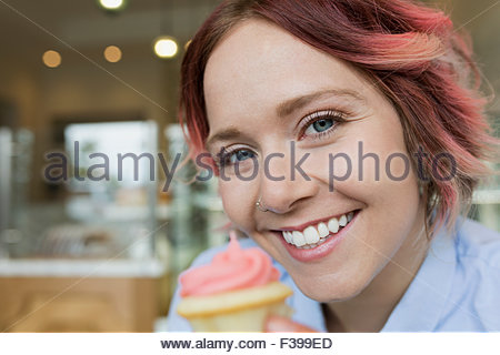 Close up portrait of smiling woman with cupcake rose Banque D'Images