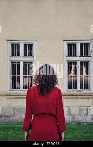 Femme en robe rouge debout à l'extérieur, vue arrière