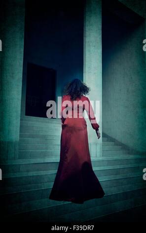 Femme en robe de soirée rouge En marche vers le haut des escaliers Banque D'Images