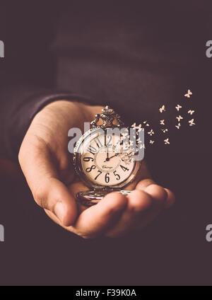 Homme tenant une montre dans sa main avec le temps de s'envoler l'horloge comme des papillons