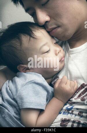 Portrait d'un homme avec ses yeux fermés tenant son fils endormi Banque D'Images