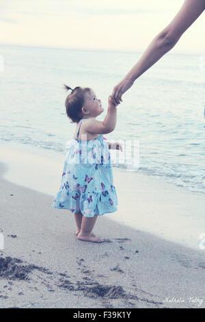 Baby Girl holding sa mère part à la plage Banque D'Images