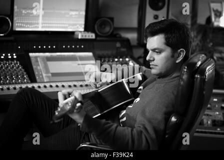Man playing guitar in recording studio Banque D'Images