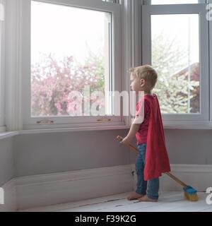 Garçon habillé comme super-héros, à la recherche d'une fenêtre Banque D'Images