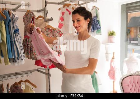 Portrait of a smiling pregnant woman dans un magasin à la recherche à l'habillement de bébé Banque D'Images