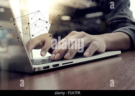 L'homme d'affaires de travail à la main sur un ordinateur portable sur un bureau en bois: le concept, le jeune Banque D'Images