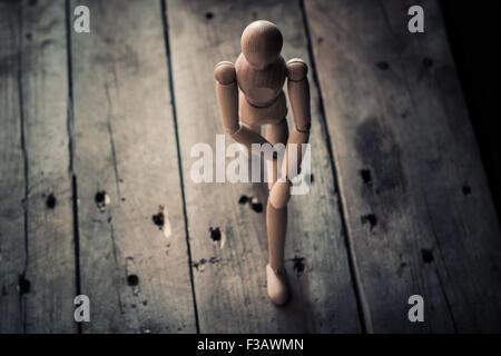 Figurine en bois debout sur une vieille table en bois. Banque D'Images