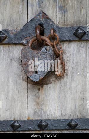 Ancien cadenas rouillés et la chaîne sur la porte en bois et fer forgé Banque D'Images