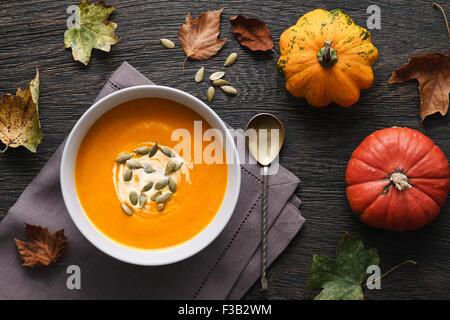 Soupe de potiron traditionnelle sur un fond de bois foncé avec les feuilles d'automne et de décoration de citrouilles.