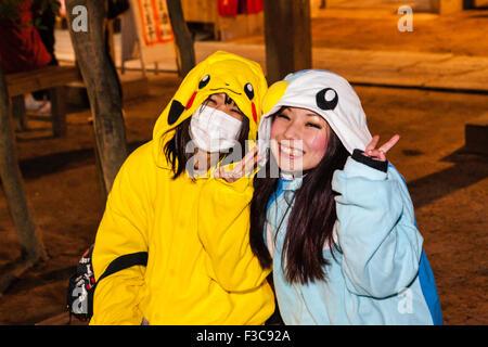 Deux jeunes femmes japonaises, l'un avec un masque, rire de spectateur et faire la paix tout en geste habillé comme Banque D'Images