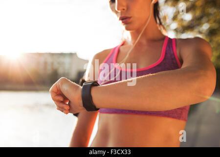 Jeune femme à sa remise en forme au smart watch tout en prenant une pause dans l'entraînement en plein air. Contrôle Banque D'Images