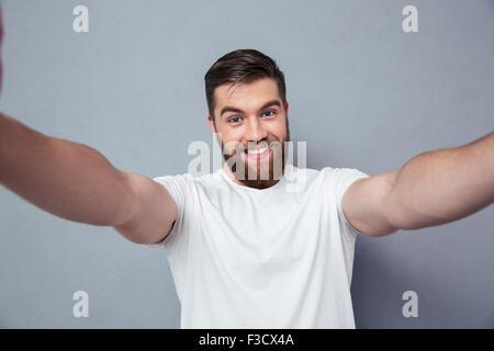 Portrait of a smiling man making photo selfies sur fond gris Banque D'Images