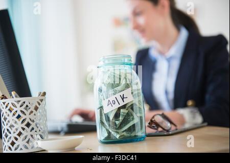Woman in office avec pot plein d'argent sur son bureau