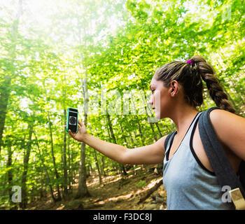 Female hiker à la boussole à sur le téléphone Banque D'Images