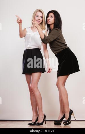 La mode et la publicité concept. Deux femmes de race blanche et de l'Afrique en pleine longueur en soulignant l'espace Banque D'Images