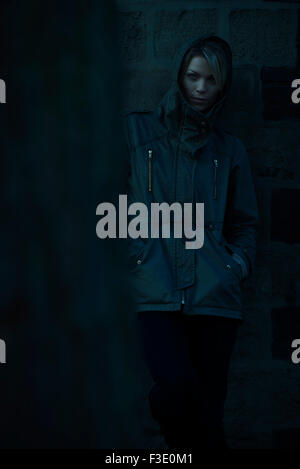 Woman wearing hooded jacke, leaning against wall outdoors Banque D'Images