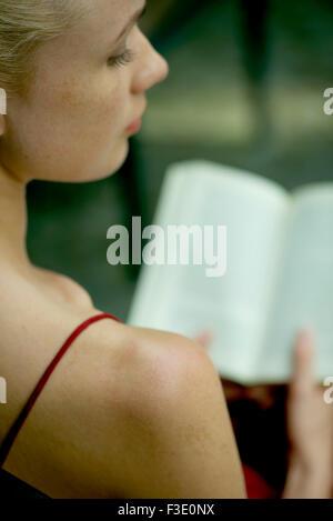Young woman reading book, sur l'épaule Banque D'Images