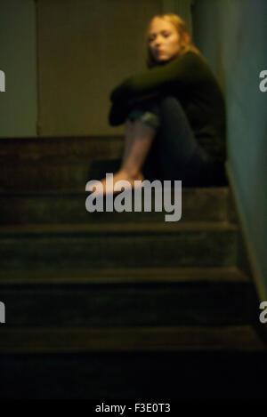 Femme assise seule dans l'escalier Banque D'Images