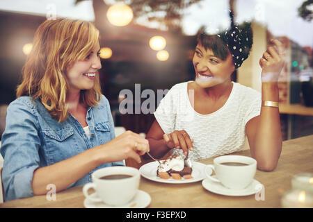 Deux jolie jeune femme bénéficiant d'un café, un gâteau ensemble dans un café assis à une table de rire et le commérage Banque D'Images