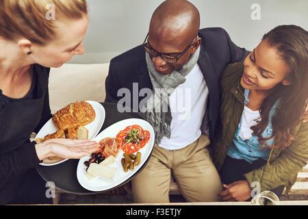 Plaqué waitress de nourriture pour young African American clients dans un restaurant, high angle view montrant la Banque D'Images