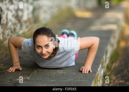 Young Girl doing push-ups au cours de l'échauffement avant le jogging dans le parc. Mode de vie sain. Banque D'Images