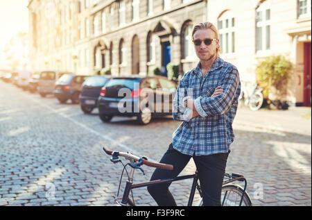 Portrait d'un homme sur son vélo avec les bras croisés à la vie élégante. Banque D'Images