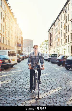 Man riding son vélo à travers la ville, Smiling at camera à la cool Banque D'Images