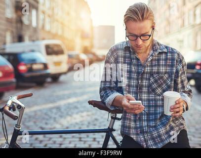Portrait plein air de jeune homme moderne avec téléphone mobile dans la rue, assis sur un vélo Banque D'Images