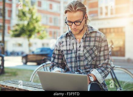 Jeune homme Concentré avec son ordinateur portable, assis à l'extérieur travailler Banque D'Images