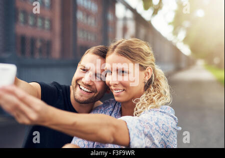 Prendre un beau couple assis Selfies dans un parc Banque D'Images