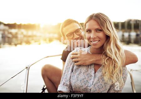 Jeune couple amoureux assis dehors sur une chaude journée d'été Banque D'Images