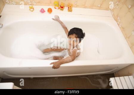 Garçon en tenant en baignoire à remous bain moussant toys à côté MR#468 Banque D'Images