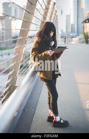 Jeune asiatique beau brun long cheveux droits femme en utilisant une tablette connectée en ligne dans la ville pendant Banque D'Images