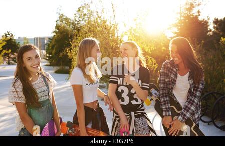 Quatre filles traînant alors que parler et rire Banque D'Images