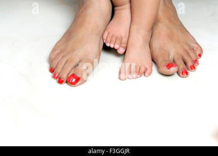 Pieds de jeunes jambes pieds bébé enfant et femme adulte mère comparaison jambes grandes et petites - M.#152 smr Banque D'Images