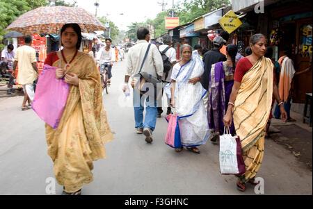 Les femmes indiennes en sari traditionnel Bengali holding umbrella á Dakshineshwar Market street Calcutta Kolkata Banque D'Images