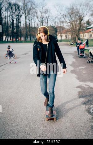 Belle jeune femme blonde sportive hipster de patiner dans un parc de la ville, à l'écoute de la musique avec un Banque D'Images