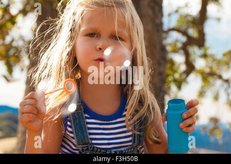 Girl blowing bubbles in park Banque D'Images