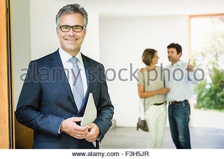 Portrait d'agent immobilier avec mature couple in new house Banque D'Images