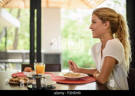 Jeune femme à la table du petit déjeuner manger des céréales Banque D'Images