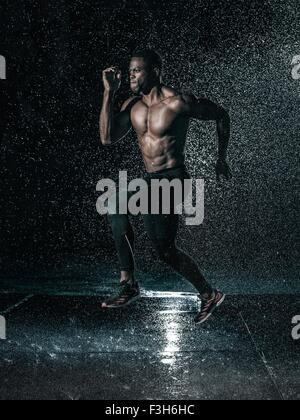 MId adult man, à l'extérieur, tournant dans la pluie Banque D'Images