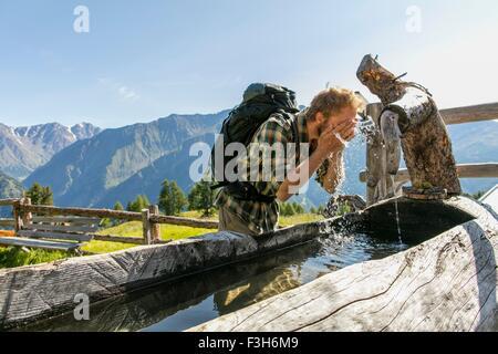 Young male hiker lave-face dans l'auge, rustique, Karthaus Val Senales, Tyrol du Sud, Italie Banque D'Images