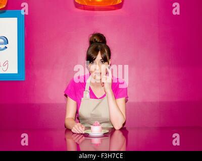 Jeune femme, qui travaillait dans une pâtisserie, assis avec cupcake en face d'elle Banque D'Images