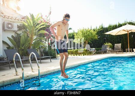 Jeune homme portant des lunettes de natation jumping into swimming pool Banque D'Images
