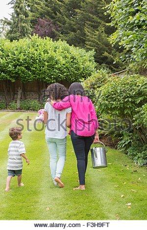 Three generation family, marchant ensemble dans jardin, vue arrière Banque D'Images