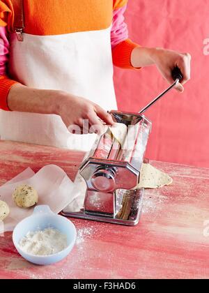 High angle view of mid adult womans mid section faire des pâtes dans la machine à pâtes Banque D'Images