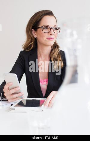 Young woman wearing eyeglasses holding smartphone looking away Banque D'Images